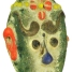 A green glass face pendant with red, yellow, and orange features 400 BC